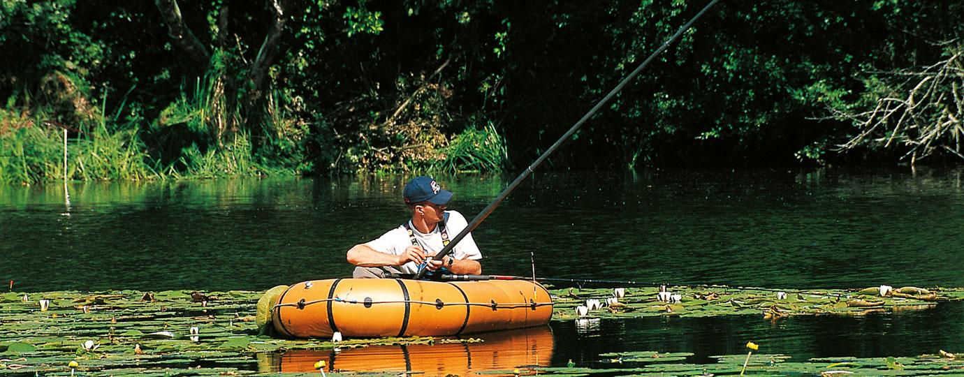 Angler im Schlauchboot zwischen Seerosen im Güstrower Sumpfsee, Mecklenburgische Seenplatte