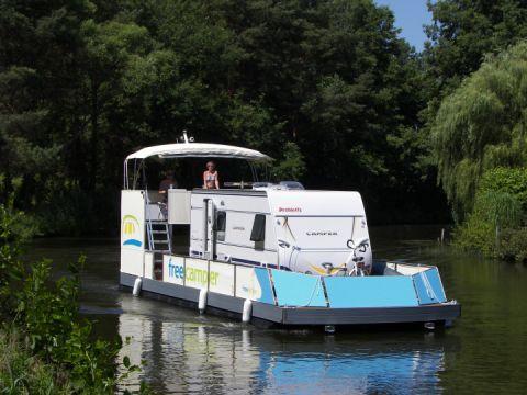 Ein freecamper mit Wohnwagen  schlängelt sich durch das Wassergebiet der Mecklenburgischen Seenplatte.