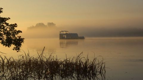Sonnenaufgang auf dem See: mittendrin ein schwimmender Wohnwagen